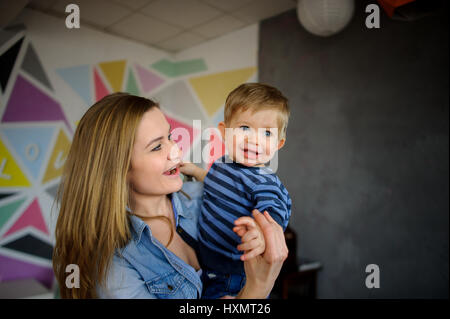 Die junge Frau hält auf den Händen der kleinen Sohn. Sie mit Liebe und Zärtlichkeit sieht das Kind. Der amüsante - Stockfoto