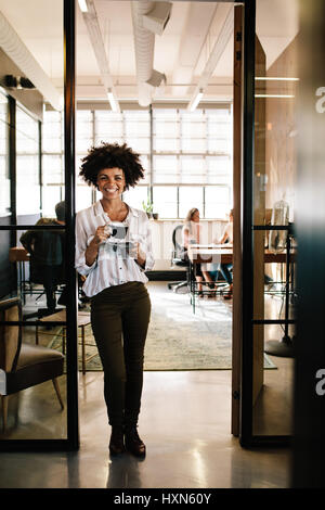 In voller Länge Portrait von lächelnden jungen Afrikanerin, die in Büro-Tür mit Kaffee stehe. Weibliche Beschäftigte - Stockfoto