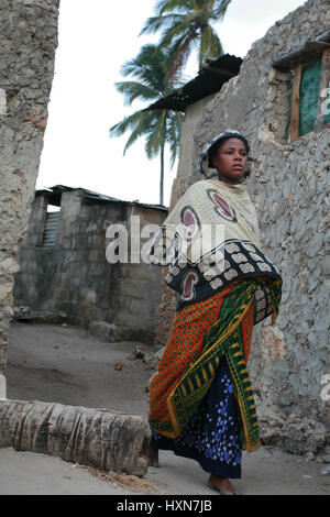 Zanzibar, Tansania - 20. Februar 2008: Unbekanntes barfußähnliches dunkelhäutige afrikanischen muslimische Mädchen im Kopftuch, ist auf einer schmalen Straße Fischerdorf.