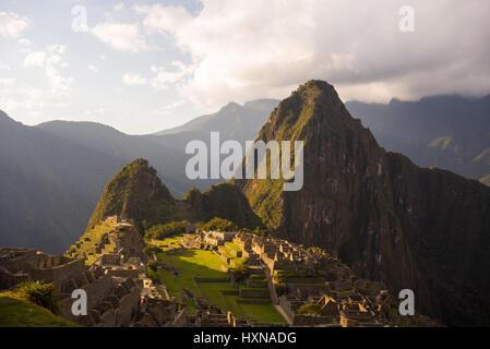 Machu Picchu teilweise durch das letzte Sonnenlicht beleuchtet. Weitwinkel-Blick von den Terrassen mit malerischen - Stockfoto