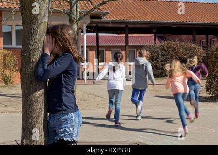 Kinder in der Grundschule spielen verstecken und suchen in Pause