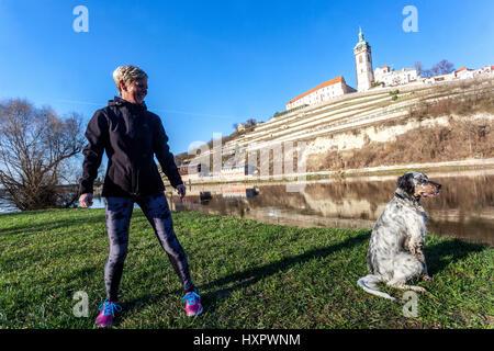 Frau auf einem Spaziergang rund um den Fluss mit ihrem Irish Red Setter, Melnik Burg im Hintergrund, Tschechische - Stockfoto