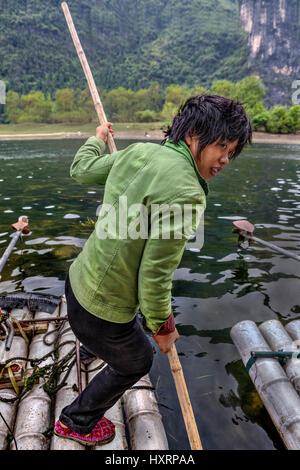 Yangshuo, Guangxi, China - 29. März 2010: Frau Fährmann Segel vom Pier, schieben Sie Stangen von unten der Fluss, - Stockfoto
