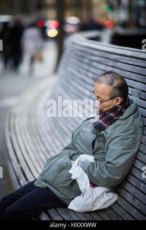 Asiatischer Mann schlafen auf einer öffentlichen Sitzbank in der Nähe von Petersplatz, Manchester City Centre, England, - Stockfoto