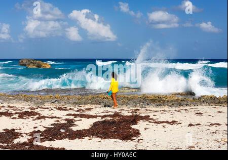 Frau Dresed in erhltlich und große Wellen auf felsigen Küste auf der Insel Cozumel - Stockfoto