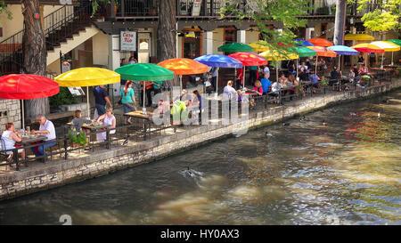 Touristen beim Mittagessen unter bunten Sonnenschirmen entlang des San Antonio River Walk in San Antonio, Texas - Stockfoto