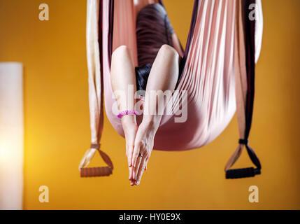 Junge Frau tut Antigravity Yoga meditativen Position in Hängematte im Studio mit gelben Wänden - Stockfoto