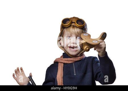 Glückliches Kind gekleidet in pilot Hut und Brille. Kind spielen mit Holzspielzeug Flugzeug. Traum und Freiheit - Stockfoto