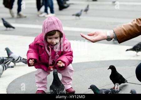 Baby in rosa Kleid, die Tauben füttern - Stockfoto