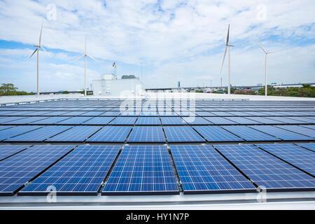 Solar-Panels auf Fabrikdach mit Windkraftanlage - Stockfoto
