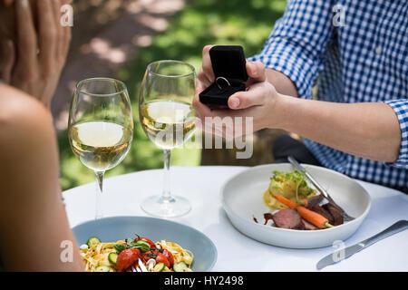Bild des Mannes zeigt Verlobungsring zu Frau im Restaurant unter freiem Himmel beschnitten - Stockfoto