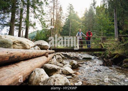 Wanderer, die Natur von einer Flussbrücke bewundern - Stockfoto