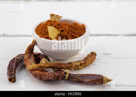 Red Chili Paprikapulver in Schüssel mit getrockneten Chilischoten auf weißen Tisch weiß