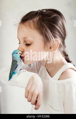 Schweden, Mädchen (8-9) Küssen pet blau vogel - Stockfoto