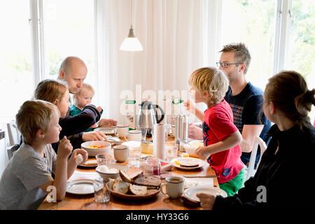 Schweden, Familie mit Kindern (2-3, 4-5, 10-11, 16-17) essen Frühstück am Tisch - Stockfoto