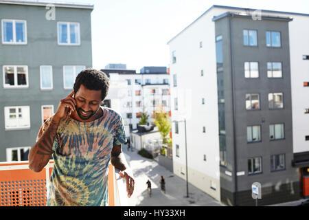 Schweden, Stockholm, Annedal, Mitte erwachsenen Mannes reden auf Smartphone auf Balkon - Stockfoto