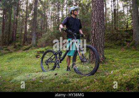 Schweden, vastergotland, lerum, reifer Mann mit Fahrrad im Wald - Stockfoto