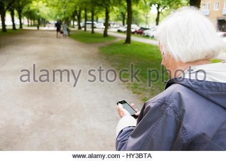 Schweden, Skåne, Malmö, ältere Frau im Park können Sie über Smart Phone - Stockfoto