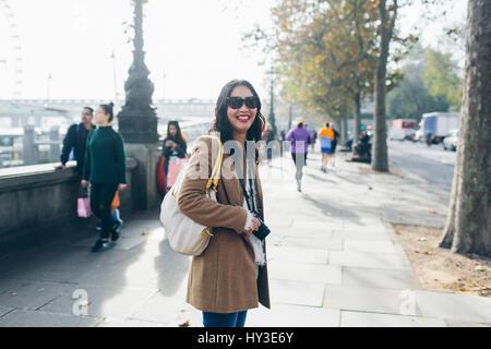 Großbritannien, England, London, lächelnde Frau stehend auf Fahrbahn in Victoria Embankment - Stockfoto