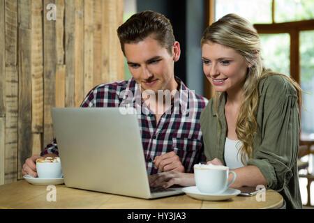 Junges Paar mit Laptop am Tisch im Café lächelnd - Stockfoto