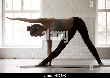 Junge sportliche Frau in Utthita Trikonasana Pose, weiße Loft studi - Stockfoto