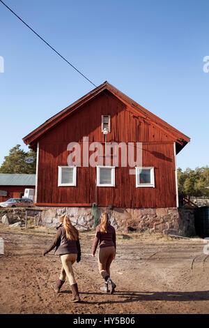 Schweden, Uppland, faringso, junge weibliche Reiter zu Fuß durch Farm - Stockfoto