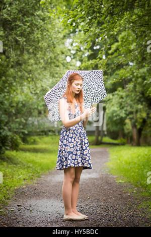 Finnland, Pirkanmaa, Tampere, Frau mit geblümten Kleid mit Regenschirm in Park - Stockfoto