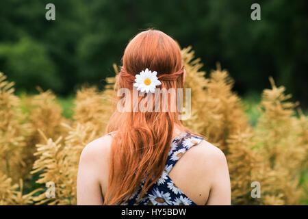 Finnland, Pirkanmaa, Tampere, junge Frau mit geblümten Kleid und Daisy Blume im Haar
