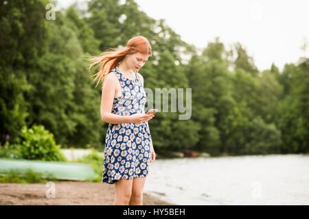 Finnland, Pirkanmaa, Tampere, Frau mit Handy stehen am Strand. - Stockfoto