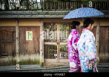 KYOTO, JAPAN - 10. Januar 2016: Japanische Frauen in traditionellen Kimonos sind Fuß unter dem Regen mit einem Regenschirm - Stockfoto