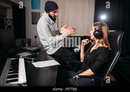 Klangerzeuger Arbeit mit Sängerin im Kopfhörer, Song-Rekord im Musikstudio. Professionelle digitale Technologien - Stockfoto