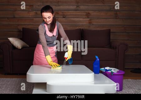 Junge Frau in Uniform und Gummihandschuhe reinigt die Tabelle. Servisce Reinigungskonzept - Stockfoto