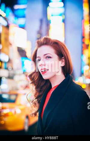 Junge Frau im roten Kleid und schwarzen Mantel ein Taxi in Times Square in New York - Stockfoto