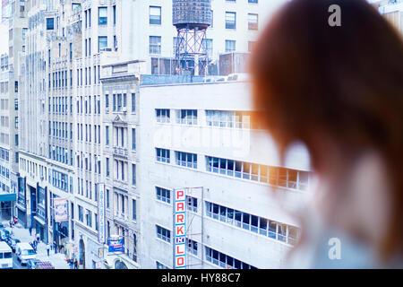 Junge Frauen sitzen an einem Fenster in New Yorker Wohnung mit Blick - Stockfoto