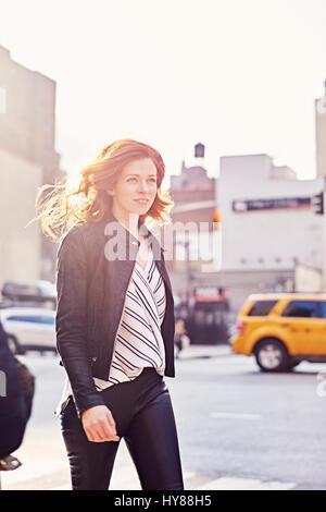 Junge Frauen, die zu Fuß entlang einer New Yorker Straße auf der Suche von der Kamera entfernt an einem sonnigen - Stockfoto