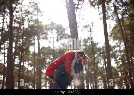 Ein Mann gibt seine weiblichen partner ein Schweinchen zurück auf einen Spaziergang im Wald - Stockfoto