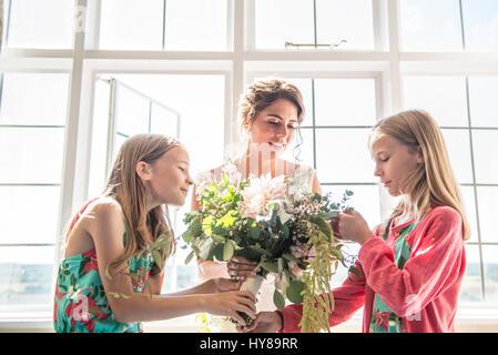 Eine Braut mit ihrem Zwilling Brautjungfern hält einen Blumenstrauß vor ihrer Hochzeit - Stockfoto