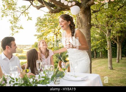 Eine Braut und Bräutigam sitzen am Tisch mit ihren Freunden bei einem externen Hochzeit - Stockfoto