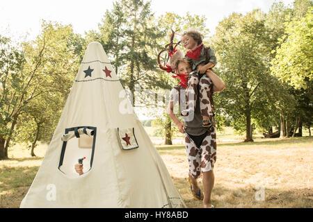 Ein kleiner Junge hebt sein Freund, während in der Sonne spielen - Stockfoto