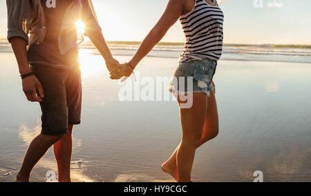Schuss von junges Paar Hand in Hand und Wandern am Strand beschnitten. Liebenden Mann und Frau am Ufer spazieren. - Stockfoto