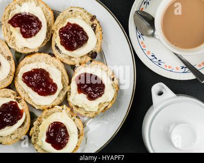 Scones mit Clotted Cream und Strawberry Jam mit Tee vor schwarzem Hintergrund - Stockfoto