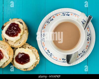Tasse Tee oder Kaffee mit Scones, Clotted Cream und Erdbeermarmelade auf blauem Grund - Stockfoto