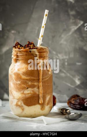 Schokolade Smoothie in Glas mit einer Banane, Termine und Süßigkeiten. Liebe für eine gesunde vegane Ernährung Konzept - Stockfoto