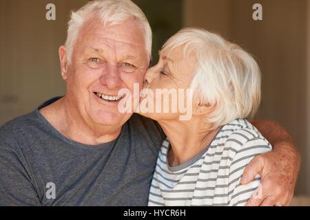 Ältere Frau küssen ihren lächelnden Mann am Morgen - Stockfoto