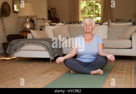 Ältere Frau sitzt im Lotussitz meditieren zu Hause - Stockfoto