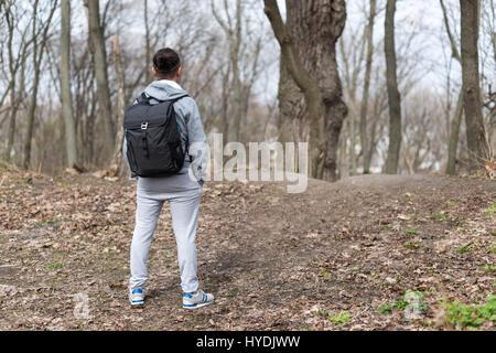 Reisender Mann mit Rucksack wandern im Frühlingswald, ruht auf dem Hügel. Reise- und Sport-Lifestyle-Konzept. Extreme - Stockfoto