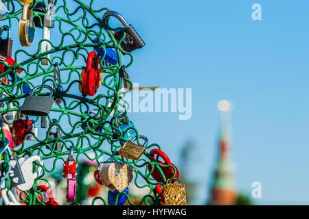 Bunte Hochzeit Schlösser auf ein Eisen-Baum. Detailansicht. Verschwommenes Bild der City Tower im Hintergrund. - Stockfoto
