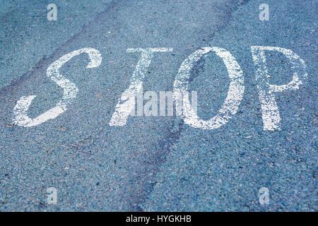 Wort zu stoppen, geschrieben auf asphaltierter Strasse, Draufsicht auf der Straße in Sicht. - Stockfoto