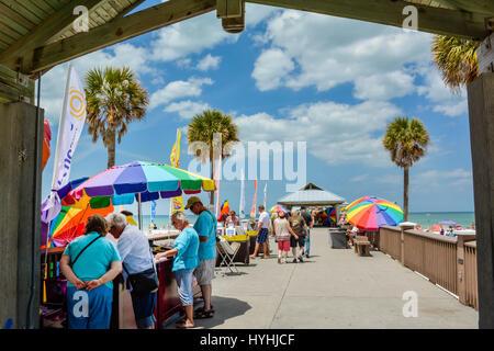 Leute, die waren von Herstellern entlang Pier 60 am Clearwater Beach, FL mit strahlendem Sonnenschein, Palmen & - Stockfoto