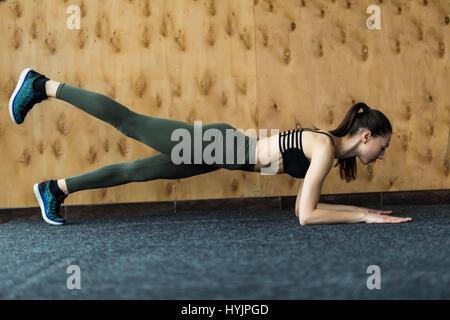 Perfekte Plank. Junge schöne Frau Sportswear tun Plank vor Fenster im Fitness-Studio steht in voller Länge Seitenansicht - Stockfoto